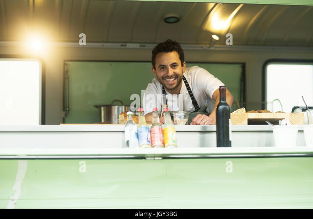 Portrait of small business owner at van food stall hatch - Stock Image