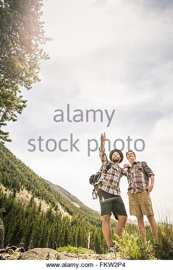 Front view of father and son trekking looking up pointing, Red Lodge, Montana, USA - Stock Image