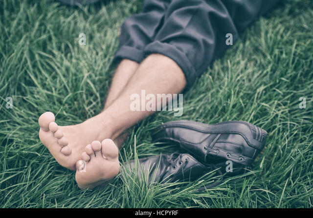 Man lying on the grass - Stock Image