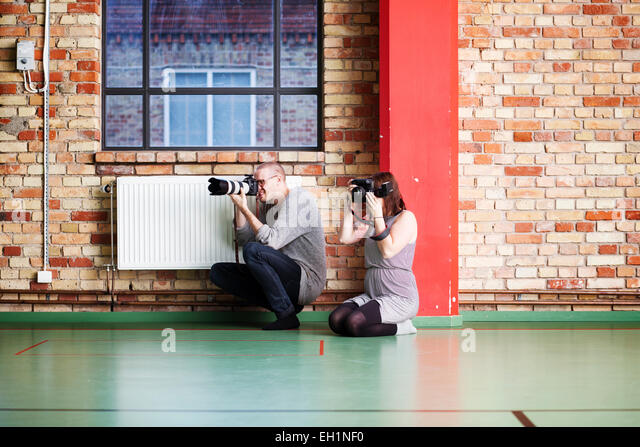 Full length of man and woman photographing in dance studio - Stock Image