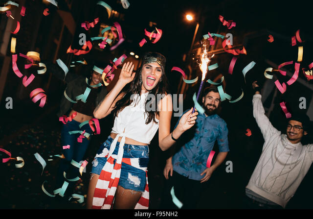 Portrait of crazy young people celebrating outdoors. Young friends partying outdoors with sparklers and confetti - Stock Image