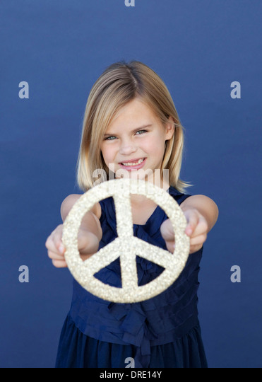 Portrait of young girl holding up peace sign - Stock-Bilder