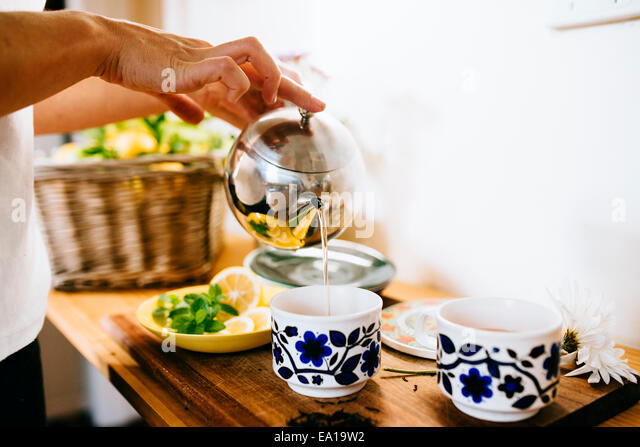 Woman preparing lemon and mint tea - Stock-Bilder