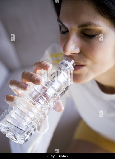 Woman sitting and drinking bottled water - Stock Image