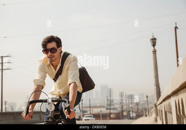 Man cycling on road, Los Angeles, California, USA - Stock Image