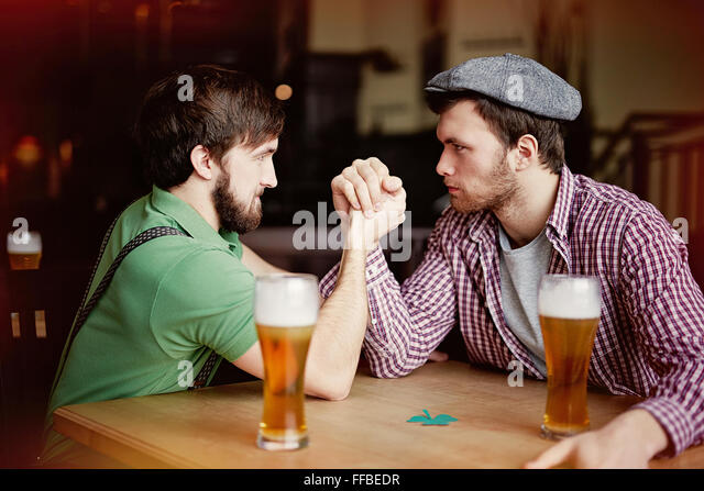 Two young men arm-wrestling while sitting in pub - Stock Image