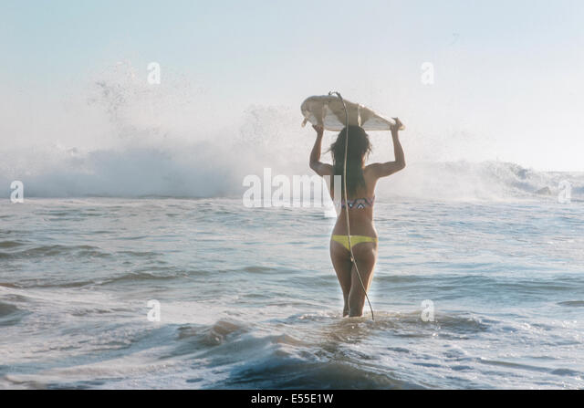 Young female surfer carrying surfboard on head walking towards crashing waves - Stock Image