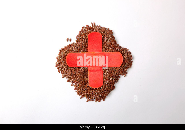 flax seeds with red cross made of bandaid over the top - Stock Image