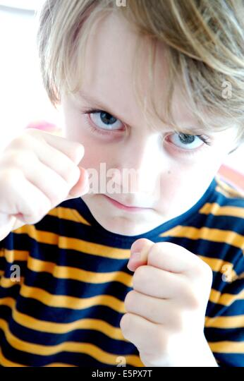 Hyperactive 5 year old boy fists raised. - Stock Image