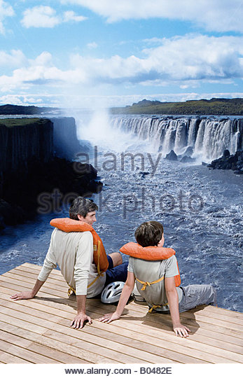 A father and son sat on a jetty looking at a waterfall - Stock Image