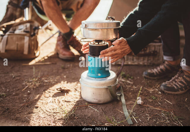 Cropped image of couple sitting at the campsite, with woman warming her hands on camp stove. - Stock Image