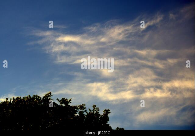 facial Pareidolia blue sky with white clouds that look like a fire dragon - Stock Image