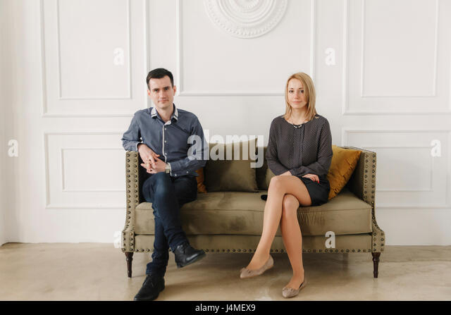 Portrait of Middle Eastern couple sitting on sofa - Stock-Bilder
