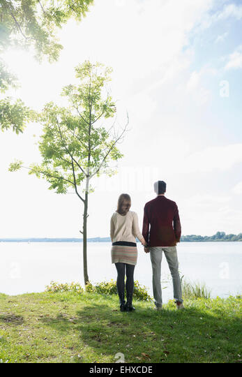 Couple holding hands lake shore romantic - Stock-Bilder