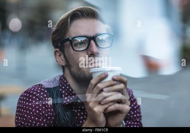 Sad young businessman behind city window drinking takeaway coffee - Stock Image