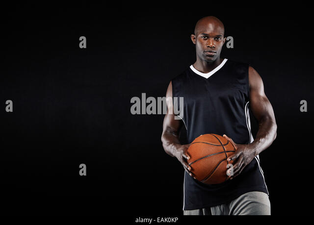 Studio shot of a young basketball player standing with his basketball. African man holding a basketball against - Stock Image