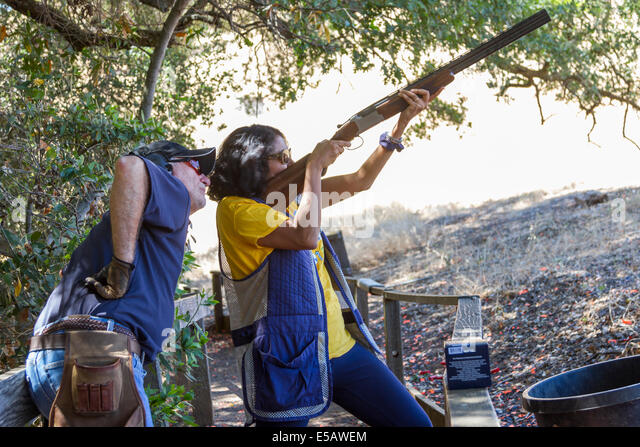 Indian woman shooting clays with a shotgun with instructor teaching her how to shoot - Stock Image