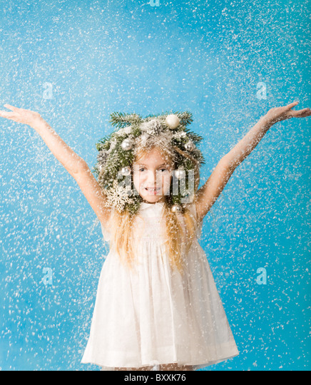 Portrait of joyful girl wearing white dress and wreath enjoying flurry snowfall - Stock Image