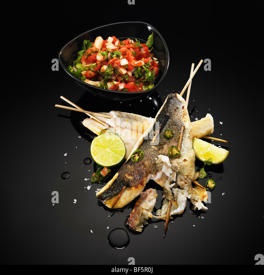 Barbecued fish skewers with lime, green chili and salad, on a black background - Stock Image