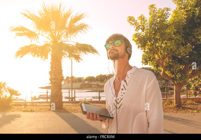 young boy on holiday using the tablet near the beach - Stock Image