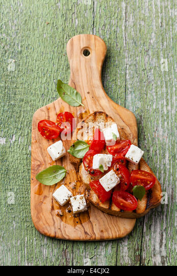 Italian bruschetta with chopped tomatoes, basil and cheese on grilled crusty bread - Stock Image