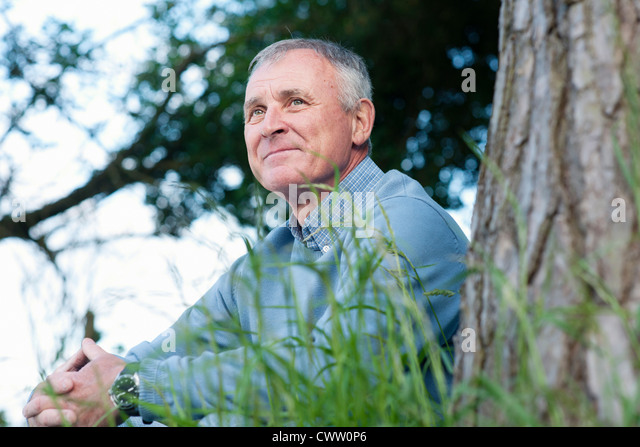 Man leaning against tree - Stock Image