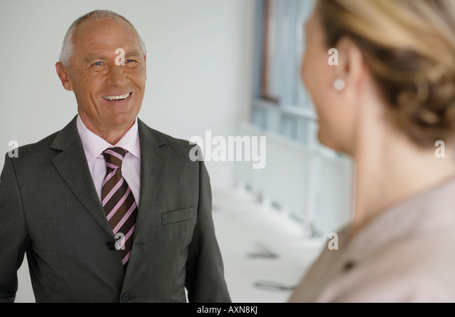 Elderly manager smiling, while talking to blond business woman - Stock Image