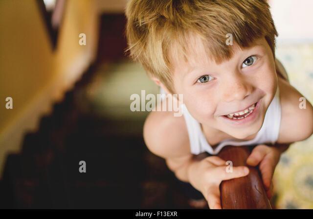 Portrait of a boy sliding down the banisters - Stock-Bilder