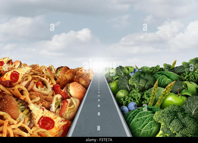 Diet lifestyle concept or nutrition decision symbol and food choices dilemma between healthy good fresh fruit and - Stock Image