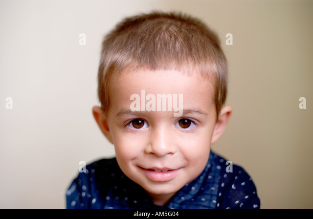 Three year old boy looks straight at the camera - Stock Image