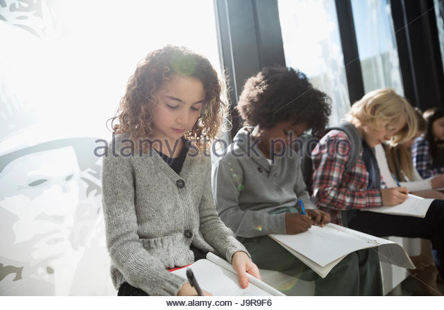 Focused girl student taking notes on field trip in museum - Stock-Bilder
