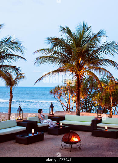 Lounging outside the Nelayan Restaurant overlooking the South China Sea at dusk. Tanjong Jara Resort. Malaysia. - Stock Image