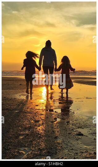 Family walk on the beach at Poldhu in Cornwall UK. - Stock-Bilder