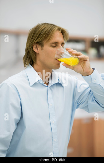Man drinking orange juice - Stock Image