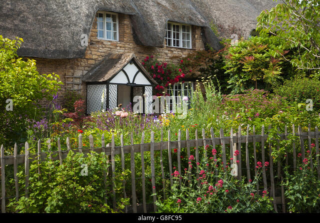 A traditional stone thatched cottage and garden brimming with colourful typical cottage garden flowers, Exton, Rutland, - Stock Image