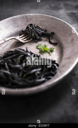 Squid ink pasta with fresh cilantro on a metal plate with antique fork. Dark rustic setting. - Stock Image