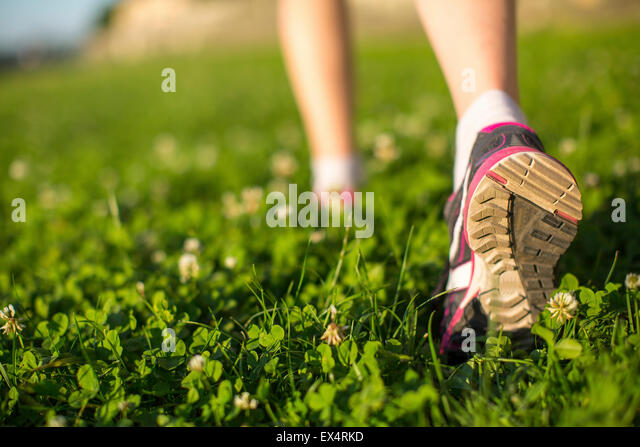 Hiker walking in the green grass outdoors, low angle close up of the foot. - Stock Image