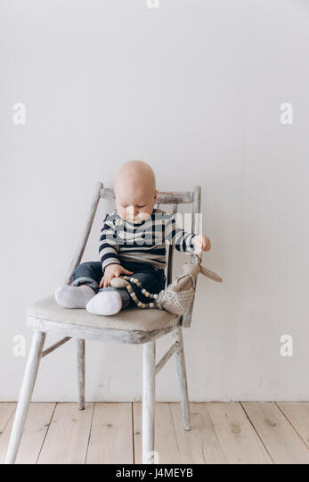 Caucasian baby boy sitting in chair playing with toy - Stock-Bilder