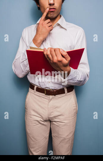Young man standing by a blue wall reading book - Stock Image