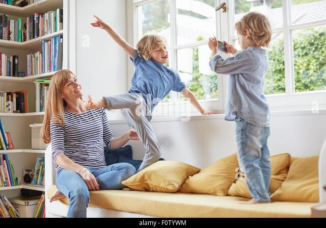 Young boy taking photograph of mother and brother, using smartphone - Stock Image