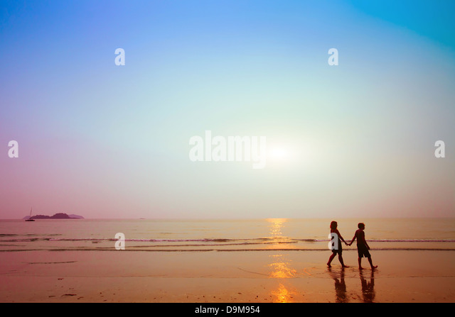 silhouettes of couple on the beach at sunset - Stock Image