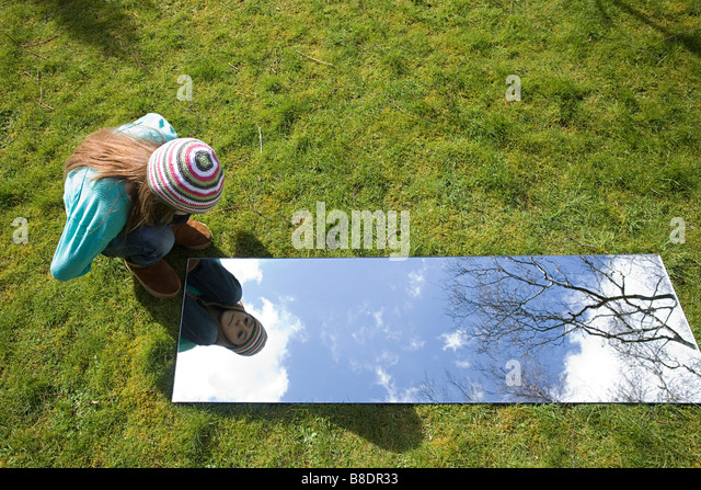 Girl looking in mirror outdoors - Stock Image