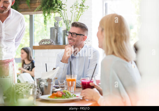 Smiling man enjoying lunch at cafe table - Stock Image