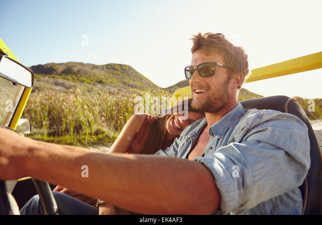 Happy young couple going on holidays together in a buggy car. Loving couple enjoying on a road trip. - Stock Image