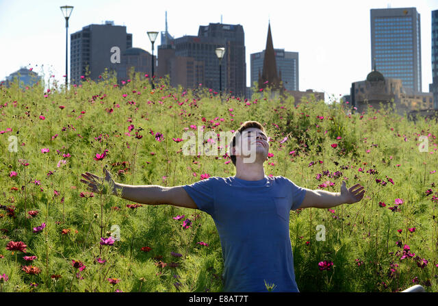 Young man, arms outstretched, against wild flowers and cityscape - Stock Image