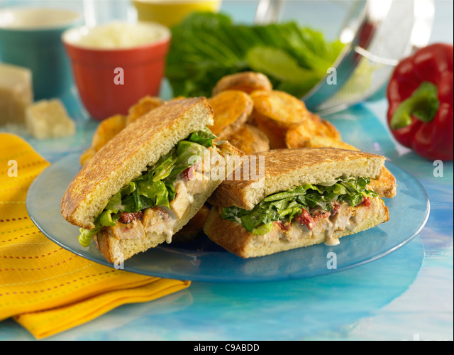 Gourmet chicken sandwich with leafy greens on grilled sourdough bread served with potatoes - Stock Image