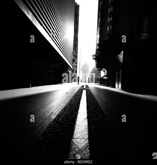 Lone figure walking along dark street with tall buildings London England - Stock-Bilder