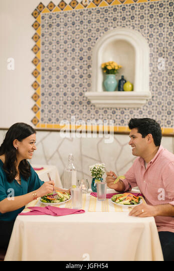 Smiling Hispanic couple eating salad and laughing in restaurant - Stock Image