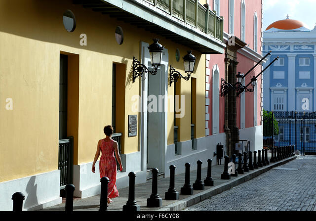 Woman and colorful Spanish Colonial facades (State Office of Historic Preservation), Fortaleza Street, Old San Juan, - Stock Image