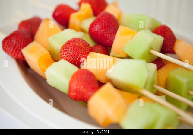 Close up of strawberry, cantaloupe and honeydew melon and fruit skewers - Stock Image